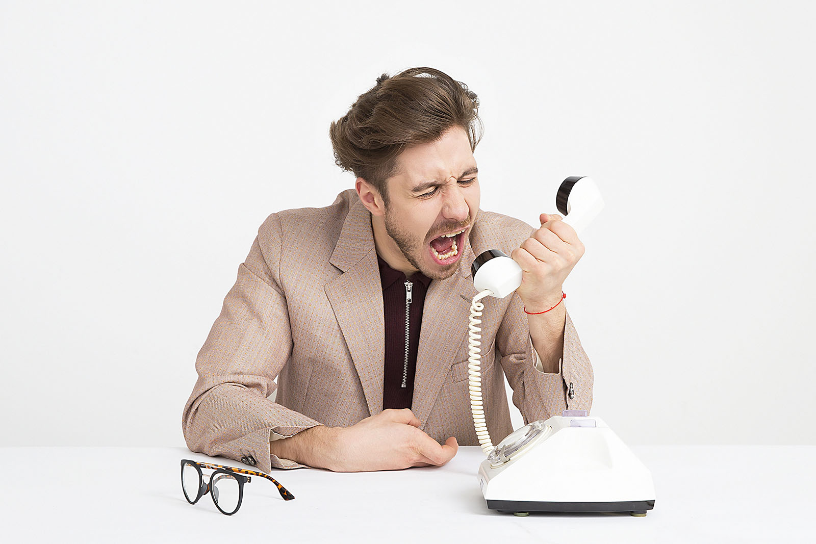 Angry man shouting through the handset of a traditional phone.