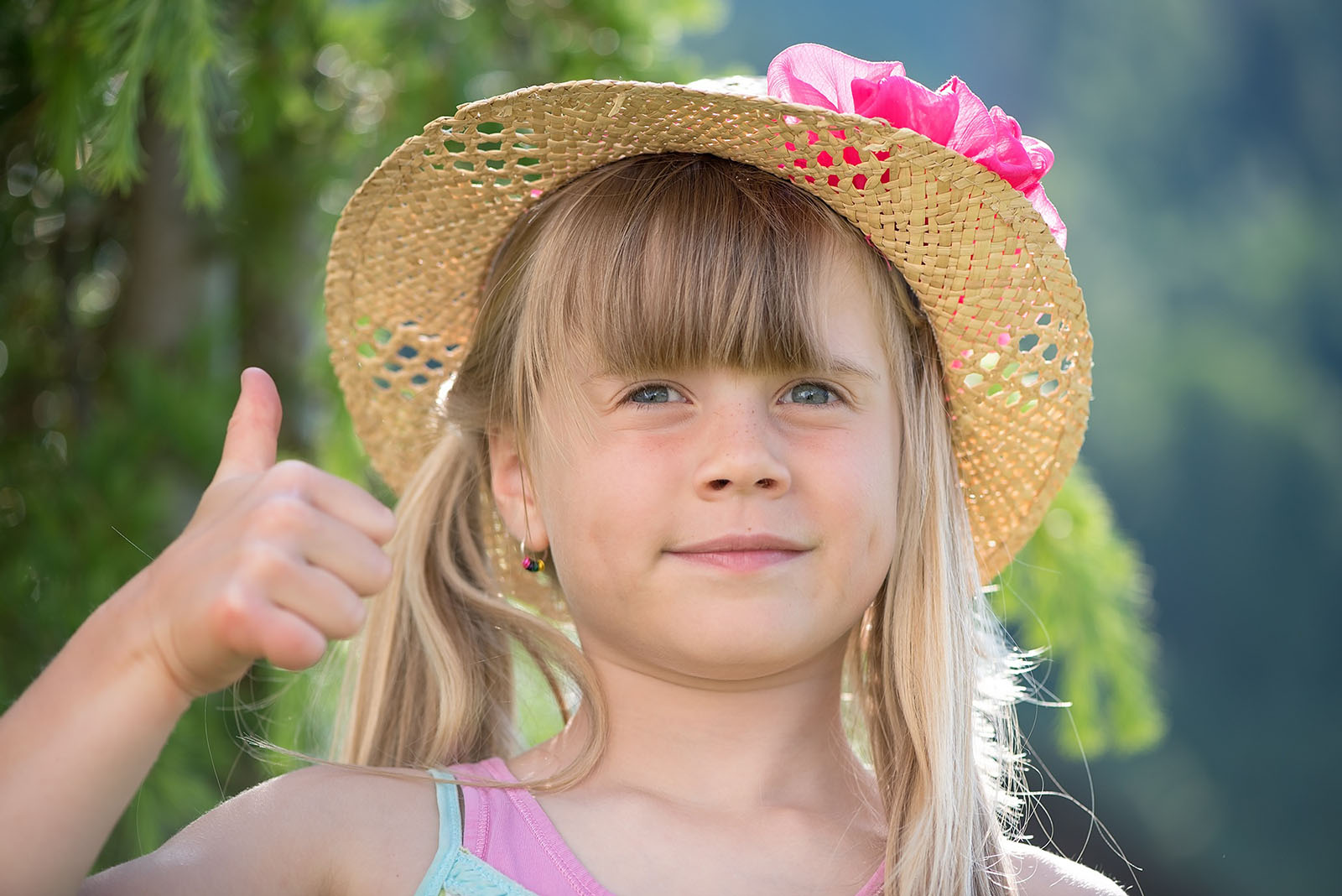 A young child with blonde hair and a summer hat giving a blank expression thumbs up to the camera.
