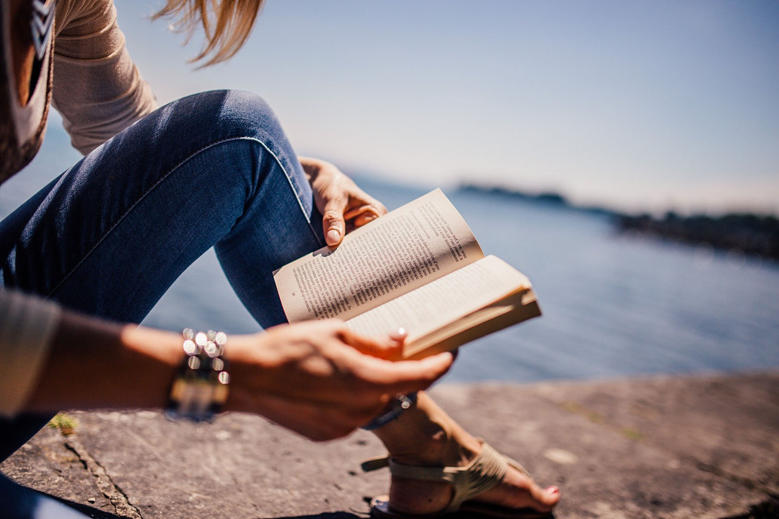 A woman reading a book on a beach.