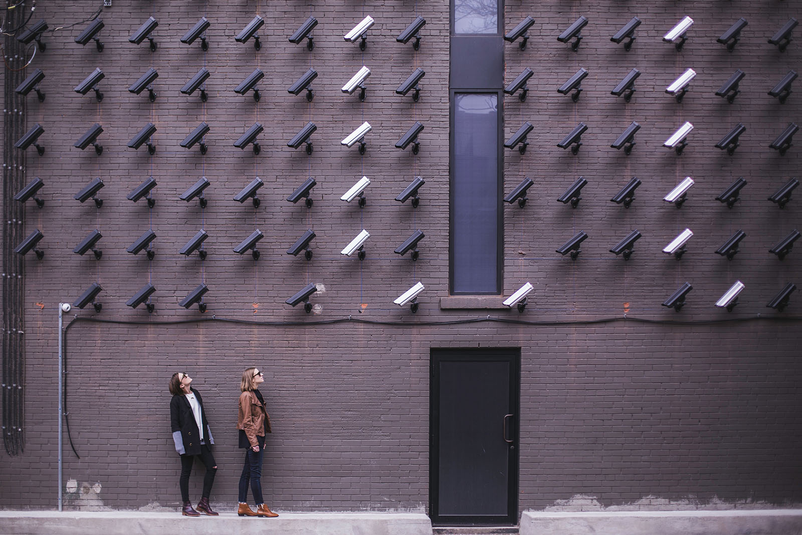 Two people look up at an abundance of CCTV cameras monitoring them.