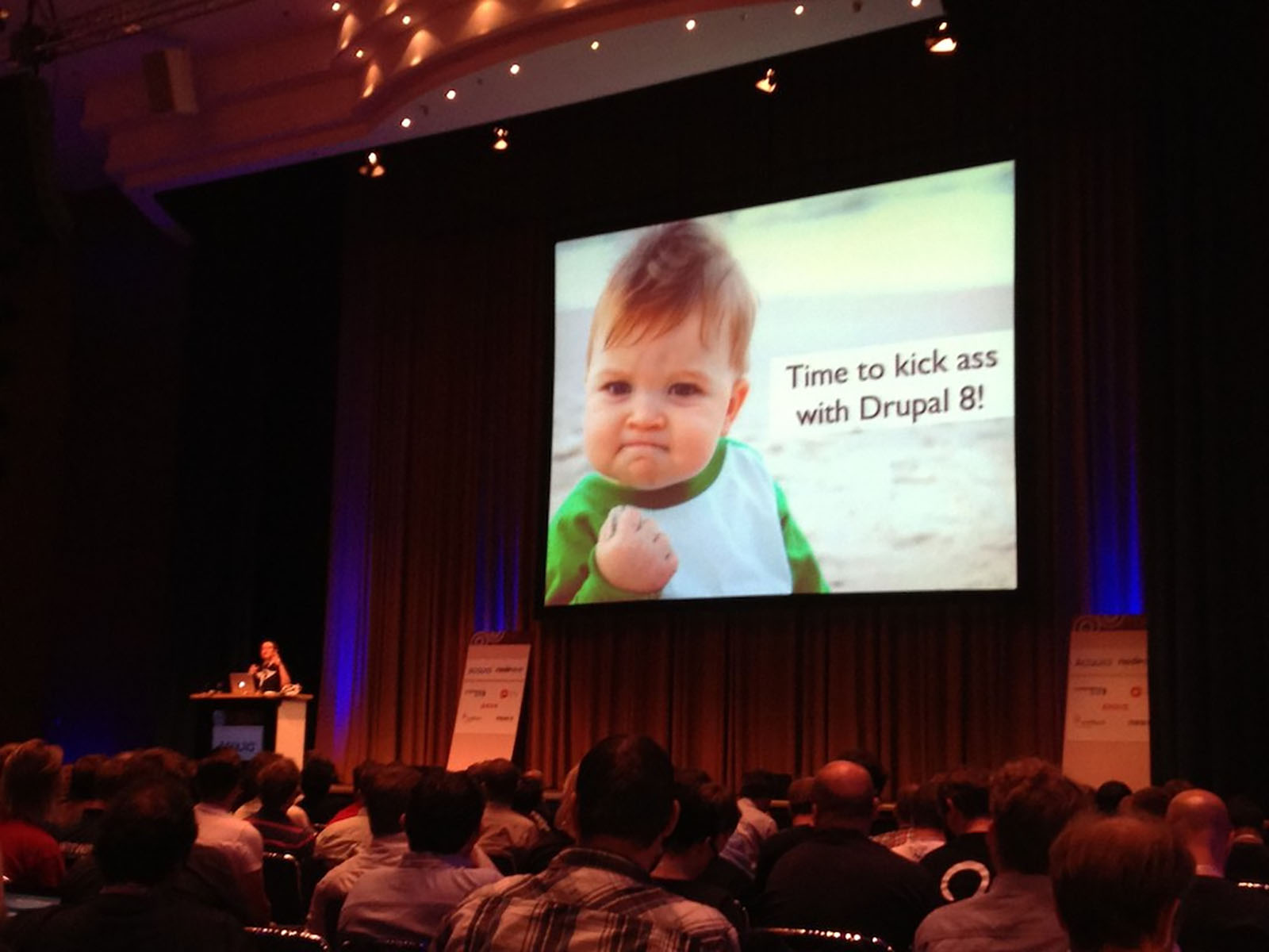 A humourous keynote slide from a DrupalCon. The slide shows a toddler clenching a fist and some wording saying 'Time to kick ass with Drupal 8'