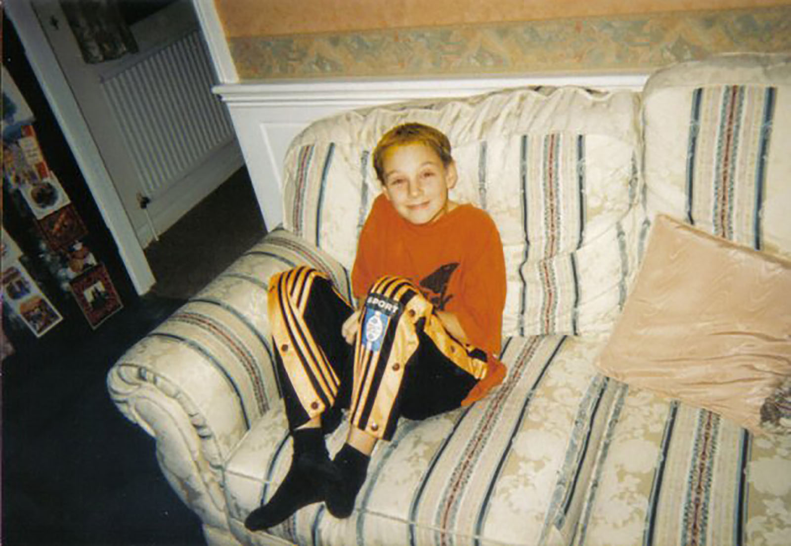 Darren as a young man (circa 10 years old) sat on a white sofa with stripes, wearing an orange t-shirt and black and orange tracksuit bottoms.
