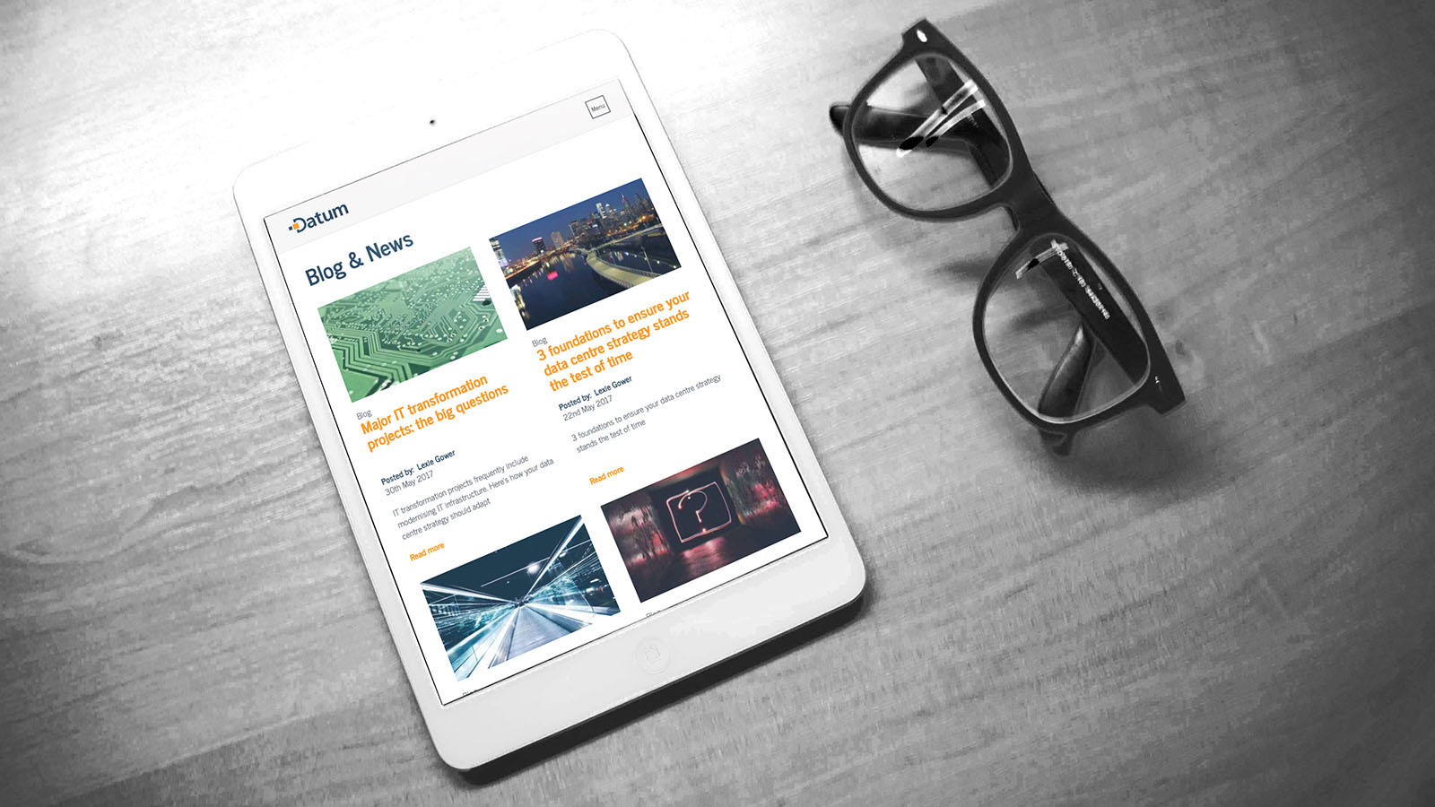 The blog page shown on an Apple iPad which is laid on a desk next to a pair of reading glasses.