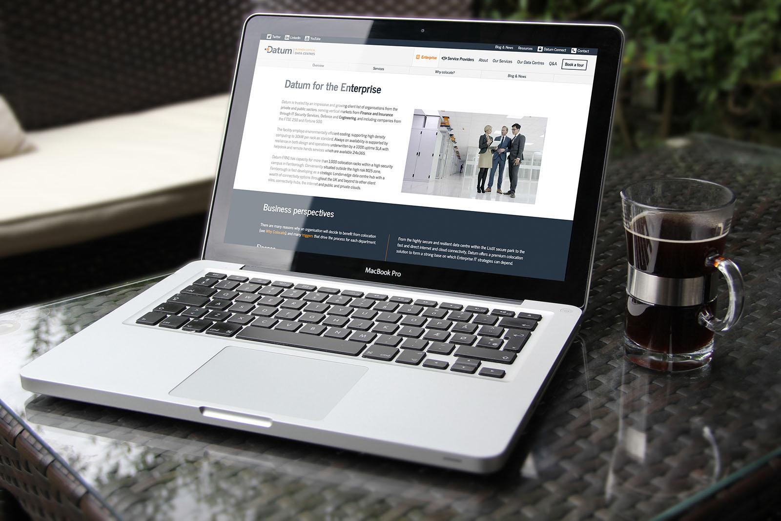The Enterprise landing page on a MacBook next to a glass of coffee.