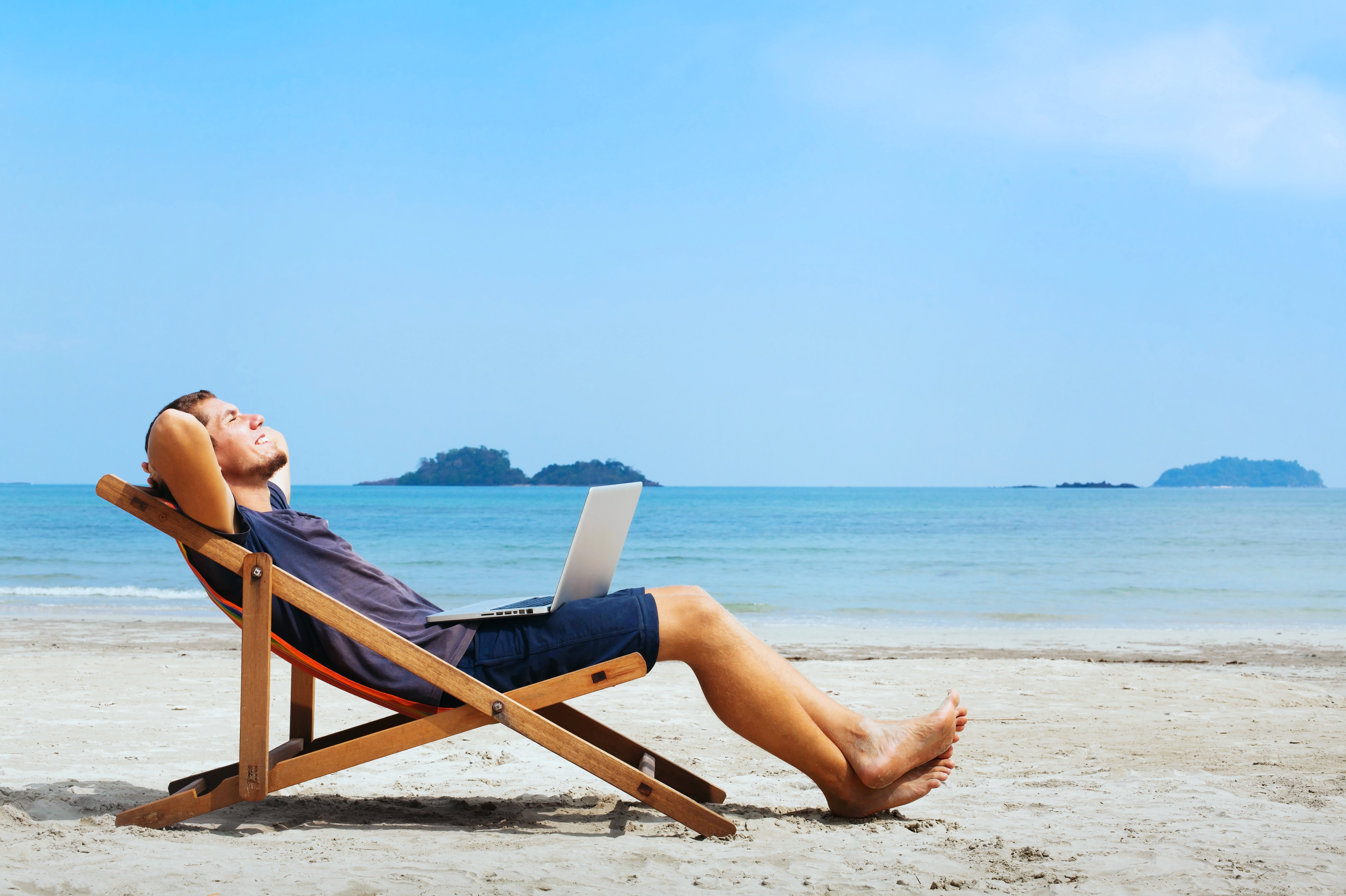 A man in shorts and t-shirt lying back in a deckchair on a white sandy beach with a laptop on his lap.