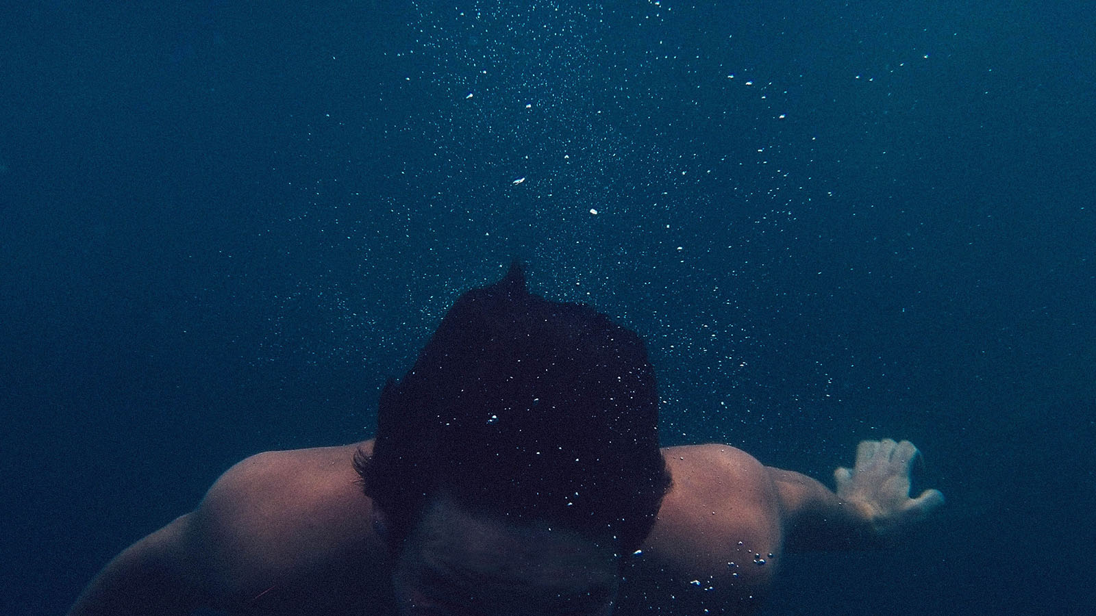 A man immersed in very deep water without breathing equipment.