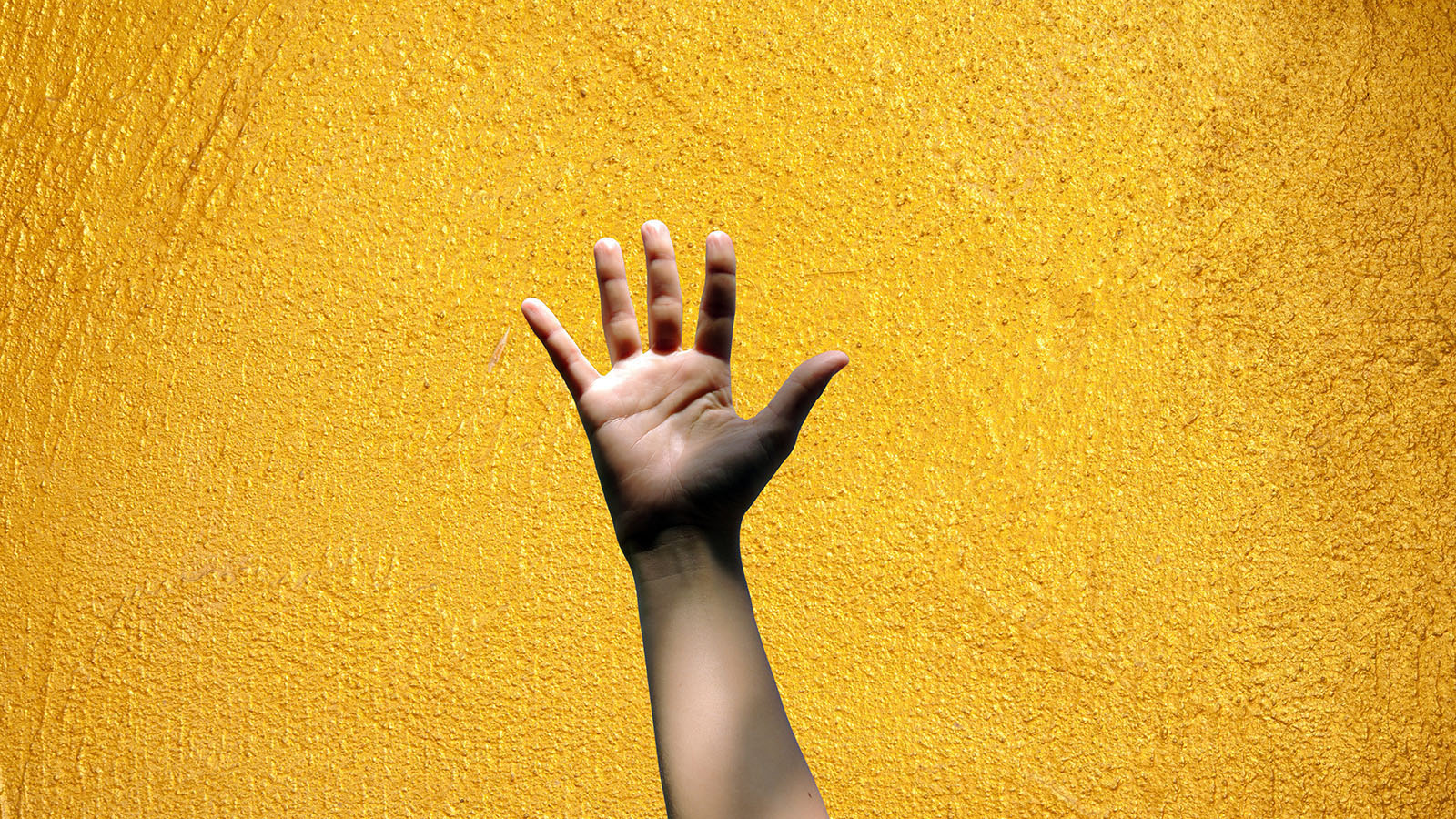 "A hand with all four fingers and thumb up signifying '5 of something'"" on a yellow gold textured backdrop."