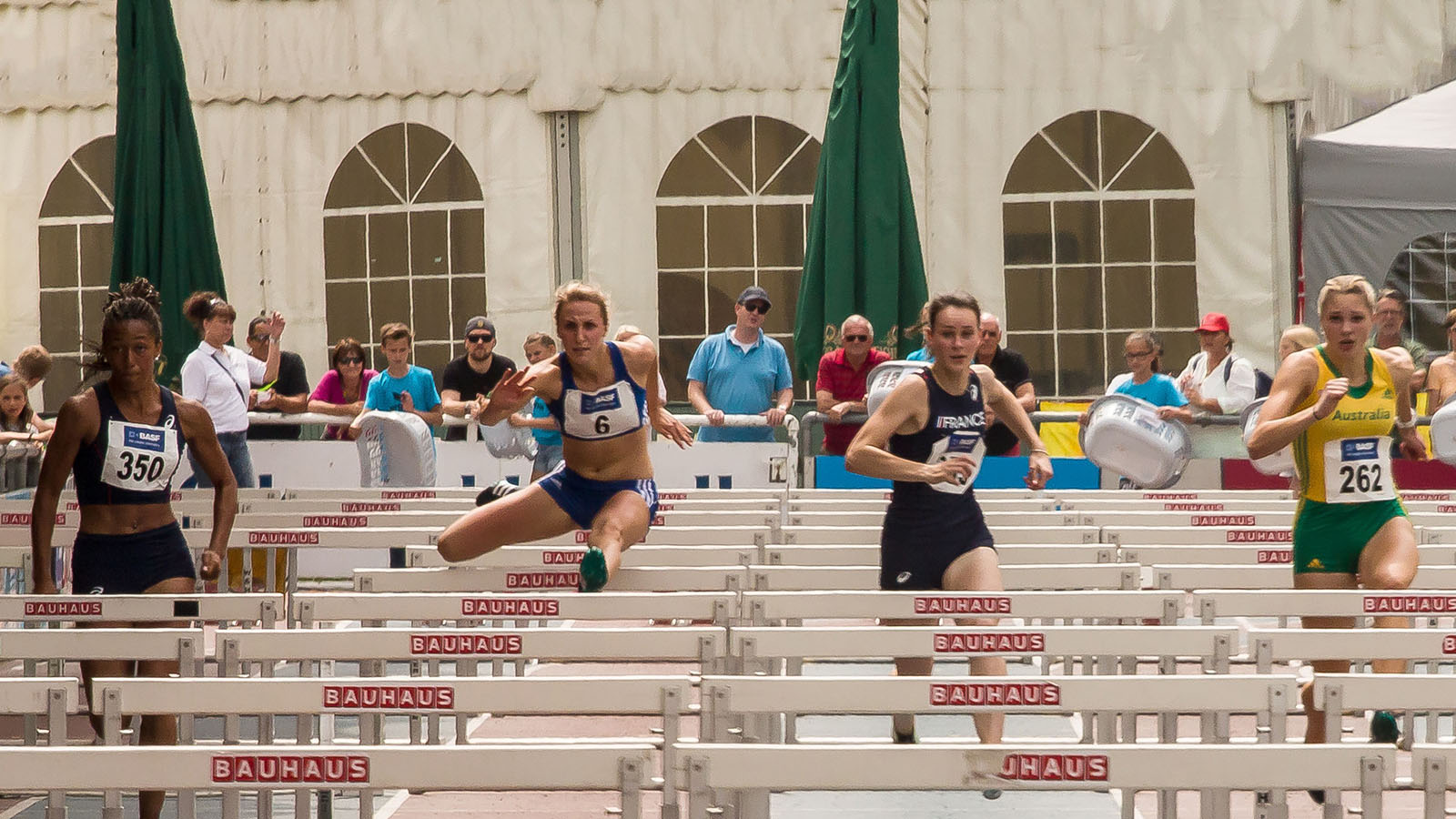 Four female hurdle sprinters are leaping over the hurdles along the race track.