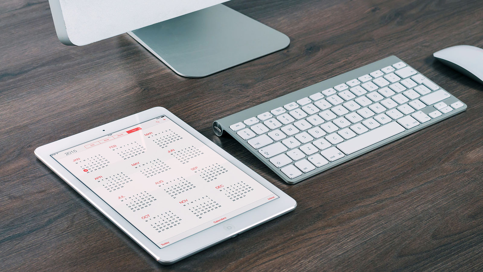 A calendar app open on an ipad laying on a desk next to an imac, keyboard and mouse.