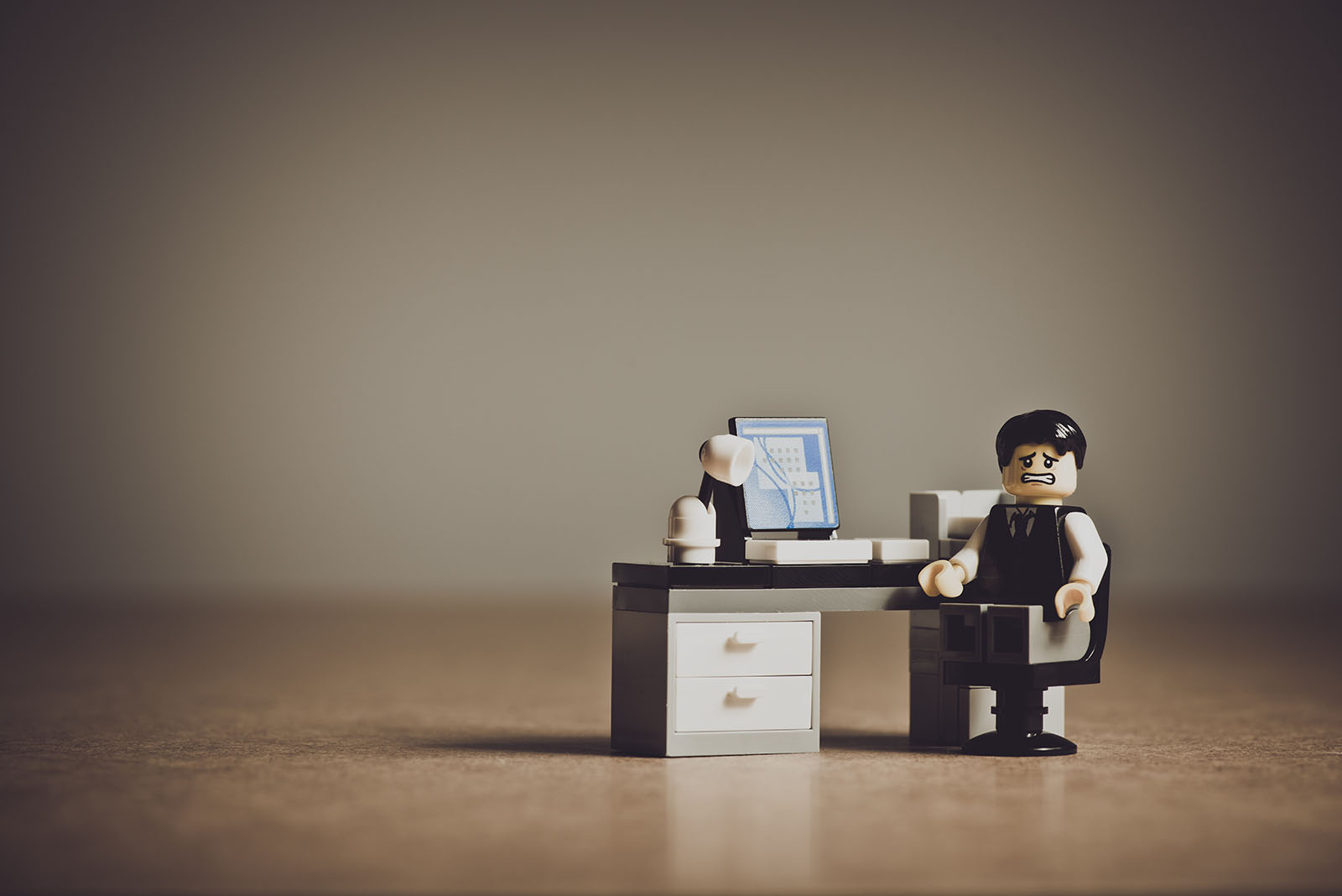 A lego man looking frustrated next to a laptop.