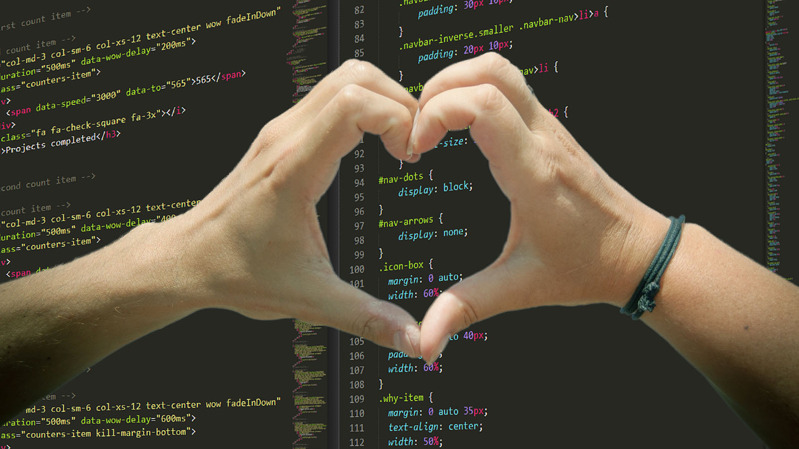 Two hands forming a heart shape with the fingers over a screen of CSS code.