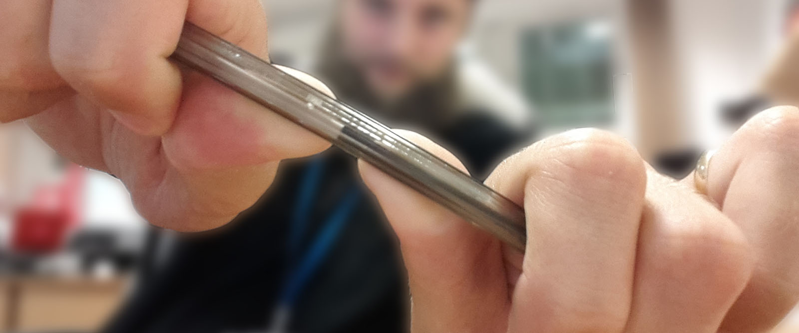 A man is holding a pen up to the camera and is in the process of snapping it in half.
