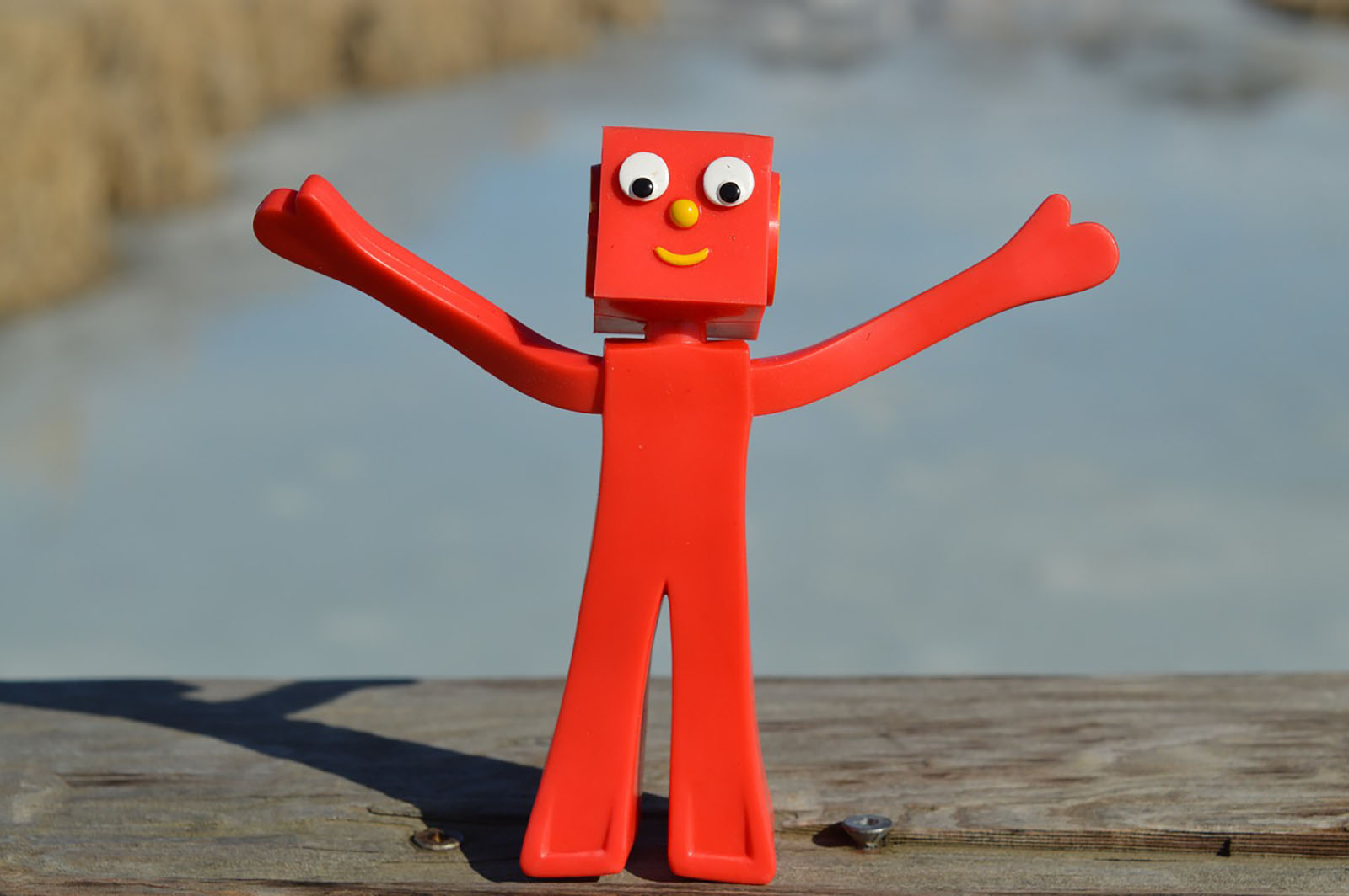 A red robot celebrating with it's arms in the air.