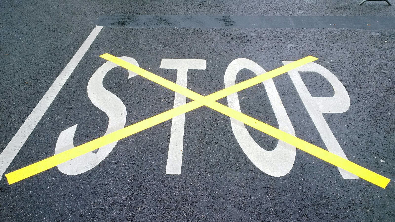 STOP painted on tarmac in white paint which has then been overpainted and crossed out with a large yellow 'X'.