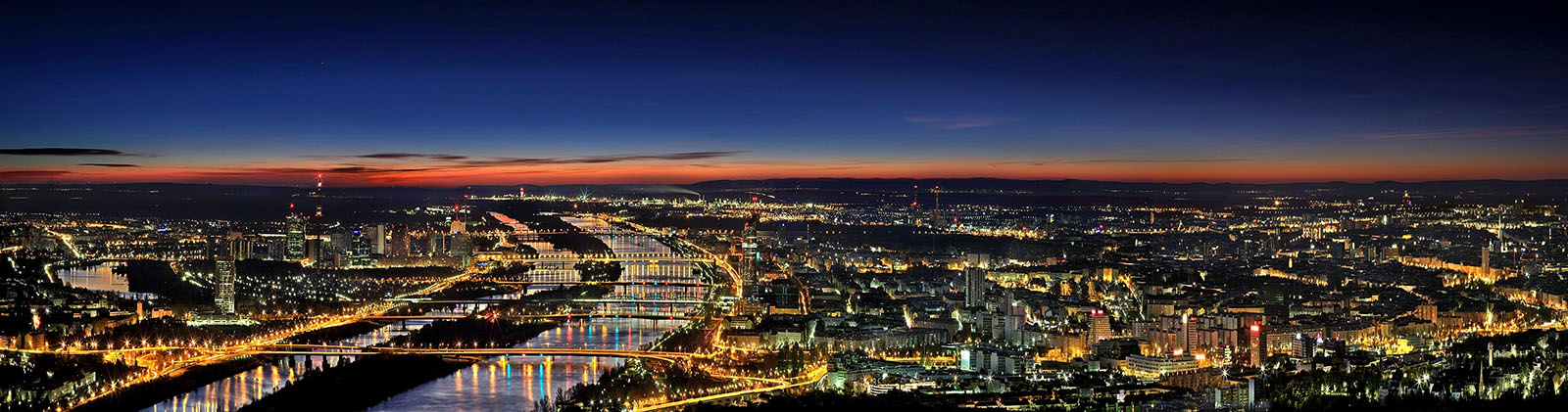 An aerial view of the Danube through Vienna at dusk.