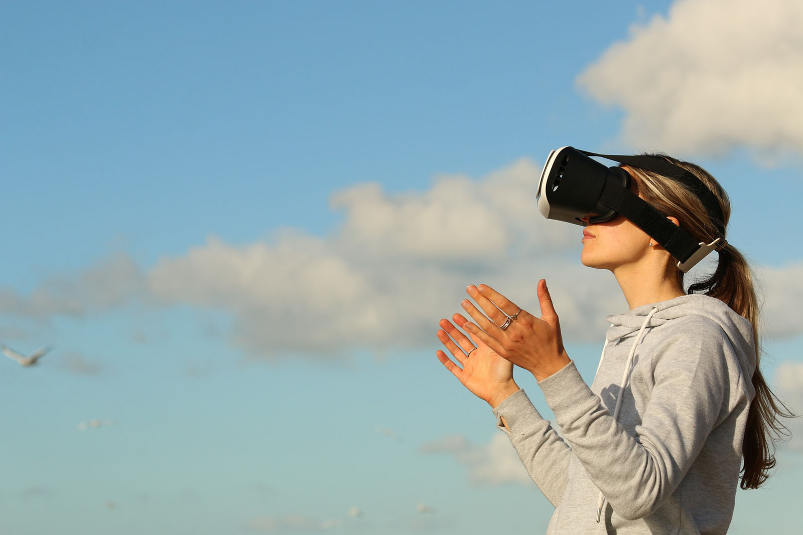 A woman wearing a virtual reality headset on a backdrop of a cloudy blue sky.