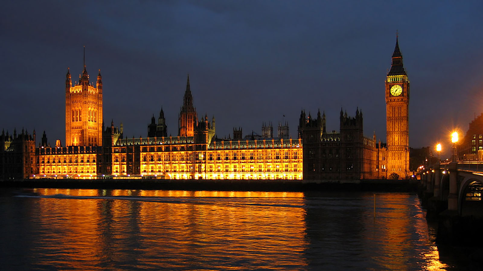 The Palace of Westminster at night seen from the south bank of the River Thames.