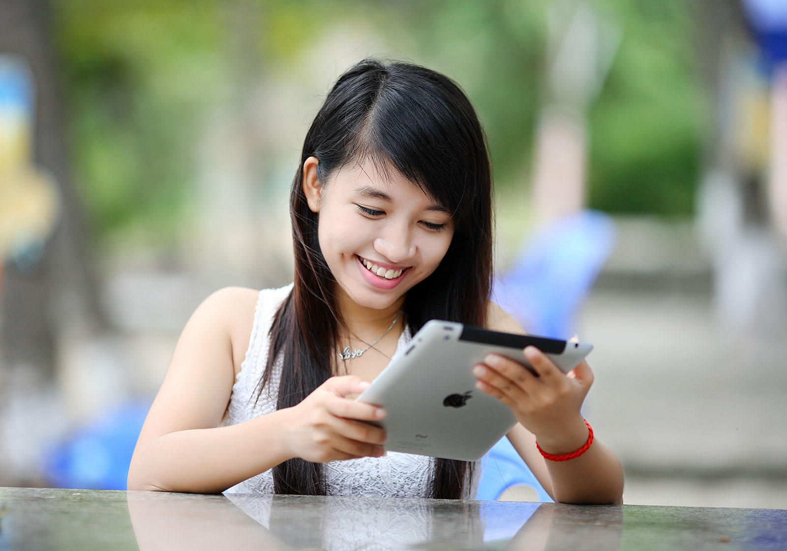 A woman smiling whilst using an ipad.